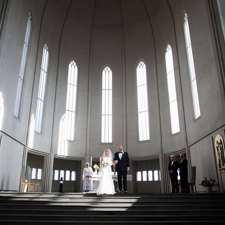Brúðhjónin standa við altarið í Hallgrímskirkju