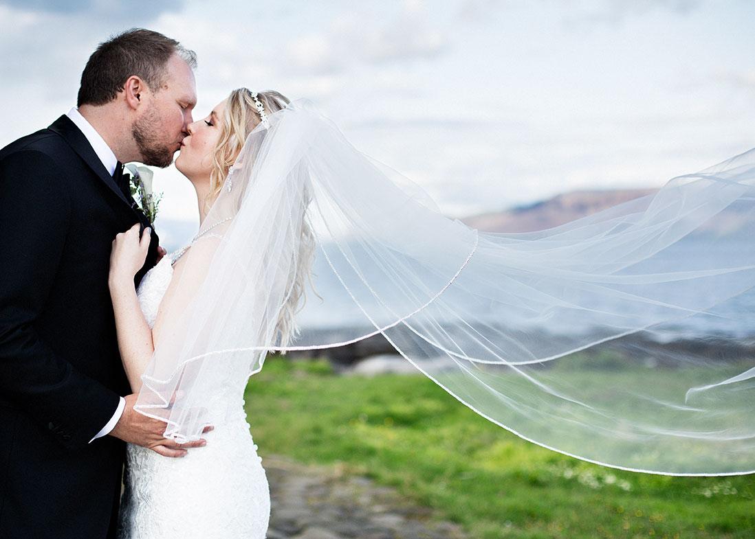 Brúðhjón kyssast og brúðarslörið