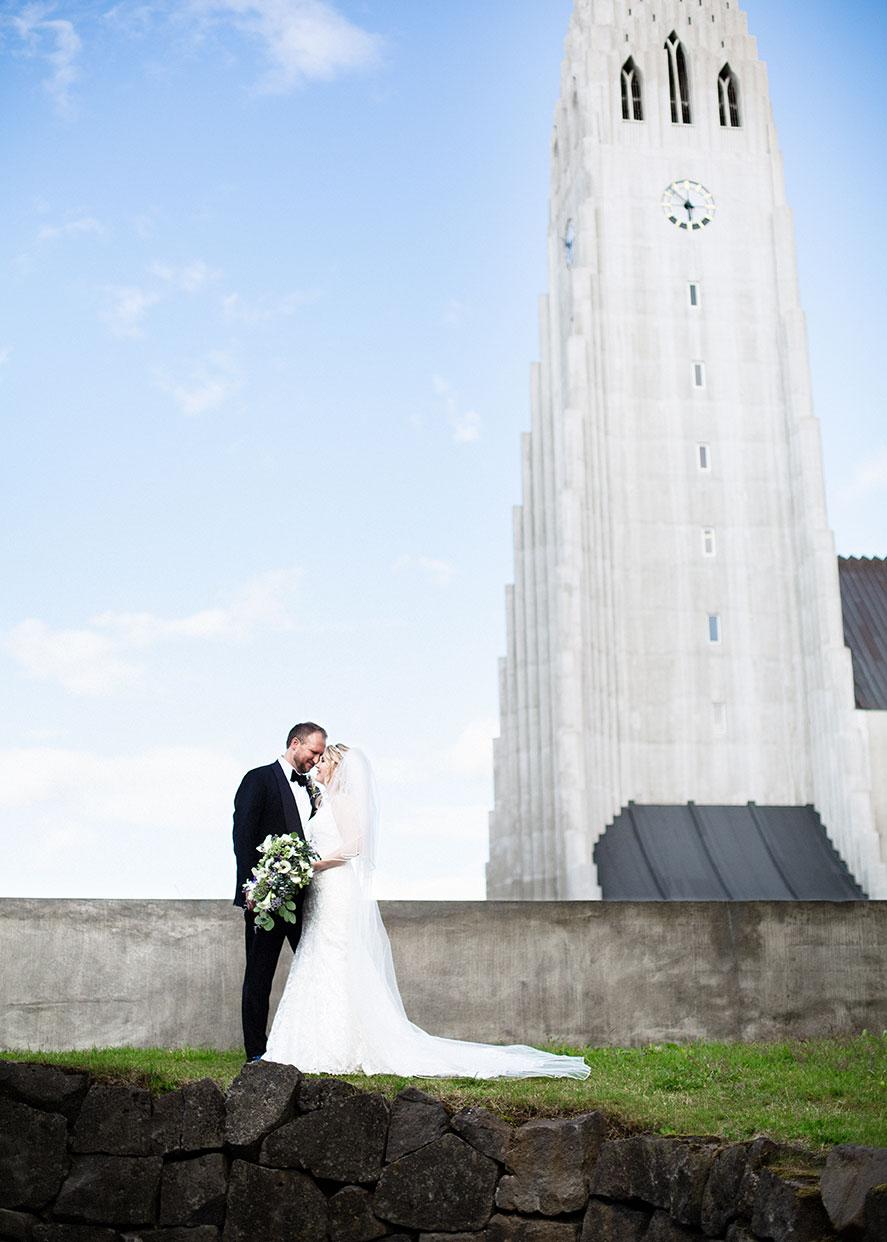 Brúðhjón standa í Listagarði Einars Jónssonar með Hallgrímskirkju í bakgrunni