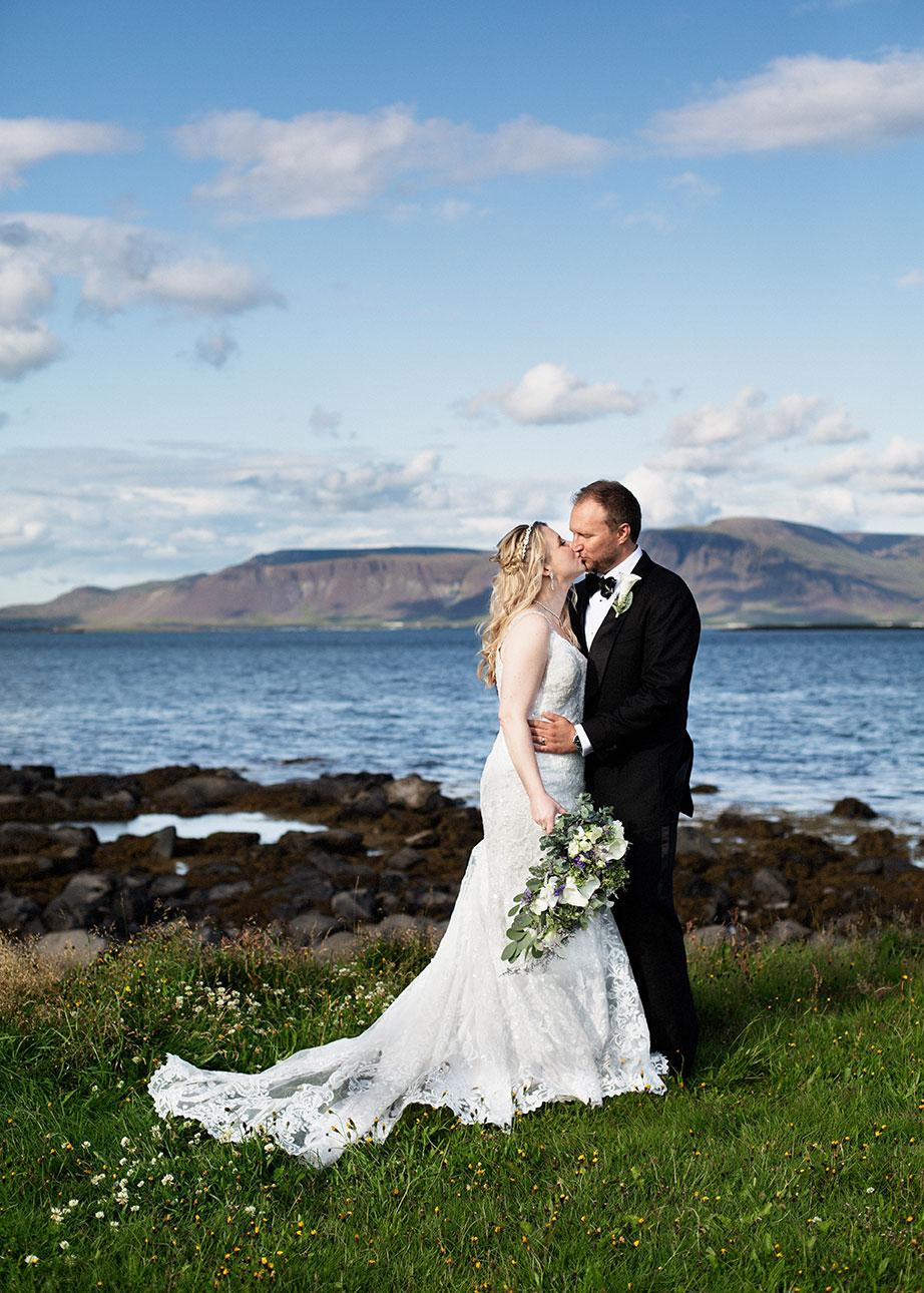 Brúðhjón standa í Gróttu með Esju og hafið í bakgrunni