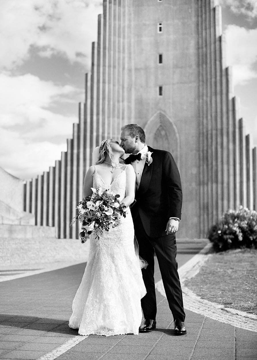 Brúðhjón kyssast fyrir framan Hallgrímskirkju