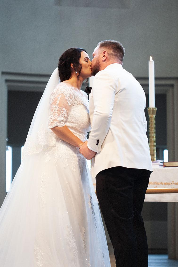 Brúðhjón kyssast við altarið í Hallgrímskirkju